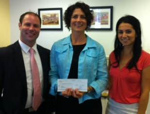 Jason Eriksen and Lauren Razaghifar of Merchant Exchange Productions present OneJustice executive Julia Wilson with the July 2013 Community Partnership donation.