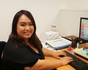Anh Van, Development Associate, sitting at her desk with computer in front of her.
