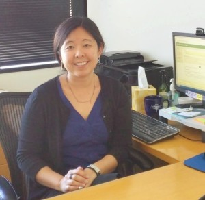 Photo of Amy Kaizuka in her office, seated at her desk with a computer screen behind her