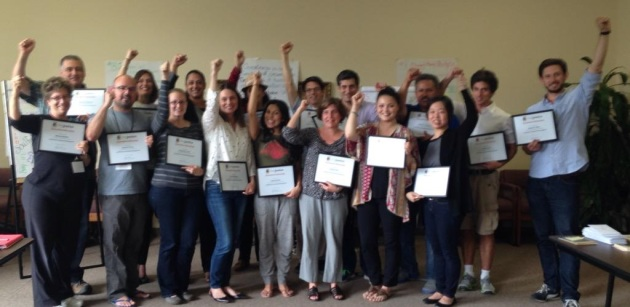 Exec Fellows Graduation Picture raising their hands and holding their certificates