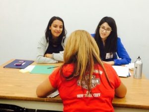 [Photo: Lowenstein Sandler LLP attorney volunteers assist a client with citizenship matters at the July 2014 clinic.]