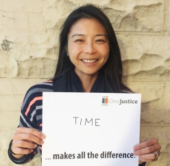 "IMAGE: Volunteer attorney holding sign that says, ""TIME makes all the difference."""